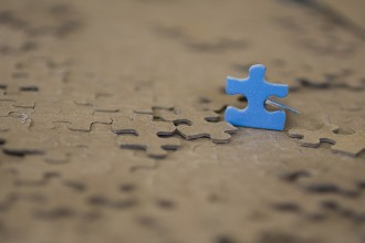 Standing Blue Puzzle Piece on brown blurred background