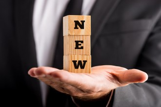 Businessman holding wooden blocks with text - New - balanced on the palm of his hand conceptual of expansion innovation and creativity in business. ** Note: Shallow depth of field