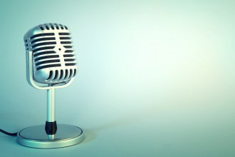 Old metal microphone on light blue background