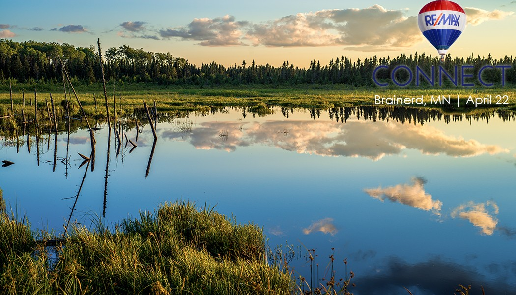 a tranquil pond refects a boreal forest and drifting clouds at sunset northern minnesota.